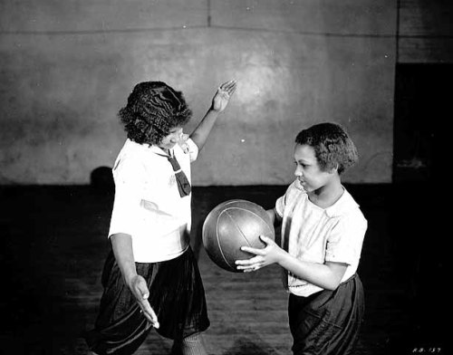 Two girls playing basketball at Phyllis Wheatley Settlement House, Minneapolis, 1925.