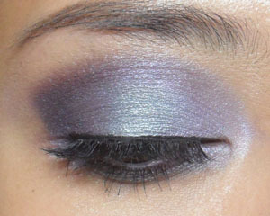 "Lavender Meadow, Lavender Storm (Revlon) —- This look features Revlon's Colorstay 12 Hours Eyeshadow Quad in Lavender Meadow. There's nothing ""meadow-y"" about these 4 shades. I personally find them more reminiscent of a surreal storm. Do beware that these shadows are sort of velvety (not highly metallic or shimmery, but not matte either) and work better over a good base.  —- Step 1: Apply a black-grey base over the lids (e.g. ELF Licorice Cream Shadow Duo)  —- Step 2: Taking the darkest shade of purple at the bottom of the quad, apply in the outer corners, bottom lash line, and up above the socket line for a very defined crease.  —- Step 3: Apply the soft aqua-steel shade (3rd from the top) right in the center of the lids. This color is what is going to give the look some interesting contrast.  —- Step 4: With the soft violet (2nd from top), apply along the inner half of the socket line, stretching out and up to meet the dark purple. Do not blend as you want the colors to all stand out a little.  —- Step 5: Apply black liquid liner and false lashes to finish the eyes.  —- And the finished look; a very colorful defined violet eye which would work for those with mono-lids."