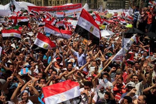 "fuckyeahmarxismleninism:  Protesters wave Egyptian flags and chant slogans as they gather in Tahrir Square, the focal point of the Egyptian uprising, in Cairo, Egypt, July 8, 2011.  Thousands of Egyptians took to the streets around the country Friday to demand justice for victims of Hosni Mubarak's regime and press the new military rulers for a clear plan of transition to democracy. The banner in the background, in Arabic, reads, ""the free people are behind bars and the killers are free."""
