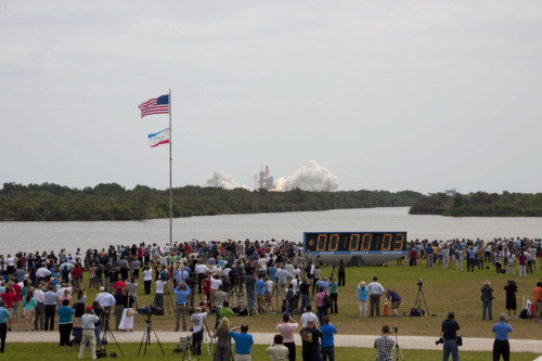 STS135-S-035 (8 July 2011) —- Members of the media and employees gather  near the countdown clock to see the launch of space shuttle Atlantis as  it lifts off Launch Pad 39A at NASA's Kennedy Space Center in Florida  at 11:29 a.m. (EDT) on July 8, 2011. Onboard are NASA astronauts Chris  Ferguson, STS-135 commander; Doug Hurley, pilot; Sandy Magnus and Rex  Walheim, both mission specialists. STS-135 will deliver the Raffaello  multi-purpose logistics module packed with supplies and spare parts for  the International Space Station. Atlantis also will fly the Robotic  Refueling Mission experiment that will investigate the potential for  robotically refueling existing satellites in orbit. In addition,  Atlantis will return with a failed ammonia pump module to help NASA  better understand the failure mechanism and improve pump designs for  future systems. STS-135 will be the 33rd flight of Atlantis, the 37th  shuttle mission to the space station, and the 135th and final mission of  NASA's Space Shuttle Program. Photo credit: NASA