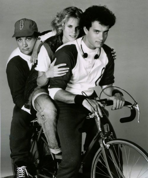 Tom Hanks, Lori Singer and James Belushi ride a bike.