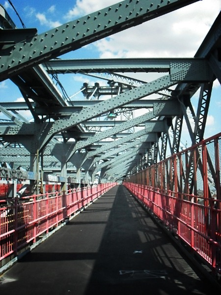 The Williamsburg Bridge pedestrian walkway, New York City   I might be a bit biased since I live so close to the Williamsburg Bridge and have crossed it quite a bit on foot but it's one of the bridges in lower Manhattan that remains close to my heart. Spanning a little over a mile, it opened in 1903 and it's one of only two bridges in New York City that carries both train and car traffic.  There is just something so oddly endearing about its steel architecture and bright red fence.    View my store, email me, or ask for help.