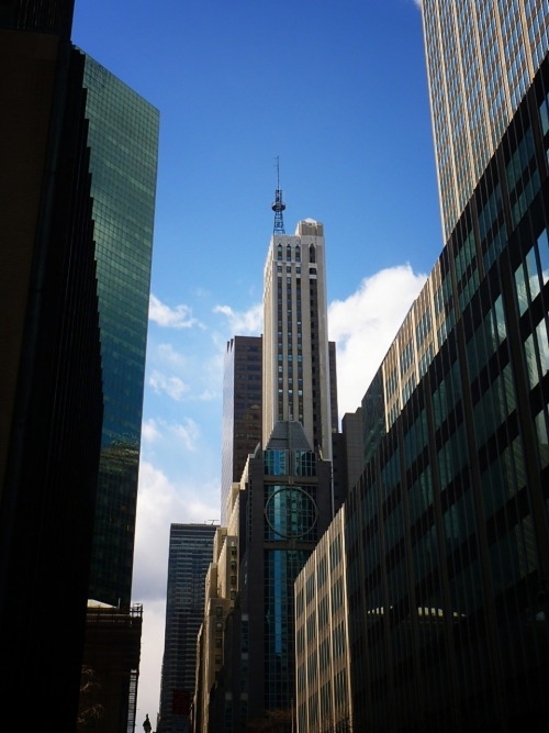 "nythroughthelens:  The Banco Santander and DuMont Buildings. Midtown, New York City. Buy ""The Banco Santander & Dumont Buildings"" Posters and Prints here, View my store, email me, or ask for help. One of the most distinctive features of the Dumont Building is its broadcasting antenna that dates back to the skyscraper's role in the first ever television broadcasts of the station WNYW in the late 1930s. ""WNYW traces its history to 1938, when television set and equipment manufacturer Allen B. DuMont founded W2XVT (re-named as W2XWV in 1944), an experimental station. On May 2, 1944, the station received its commercial license — the third in New York City — on channel 4 as WABD after DuMont's initials. It was one of the few stations that continued broadcasting during World War II, making it the fourth-oldest continuously broadcasting commercial station in the United States."" Source"