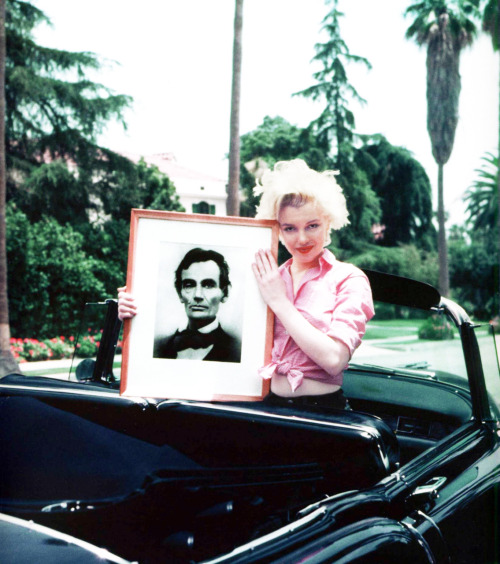 Marilyn Monroe holds up a picture of Abraham Lincoln, one of her heroes. Picture by Milton Greene 1954