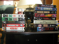 cinematicwasteland:  Some random VHS scattered upon an end table in my basement.