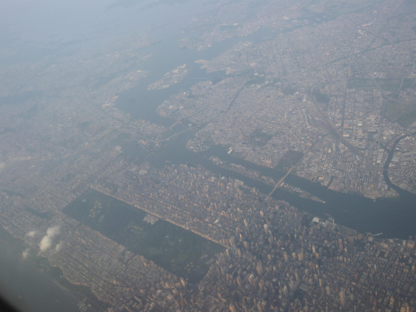 Manhattan from above, as you approach JFK. That long rectangle in the middle is Central Park. Roosevelt Island is that thin slip of land between Manhattan and Brooklyn/Queens at the top of the photo. Whattatown!