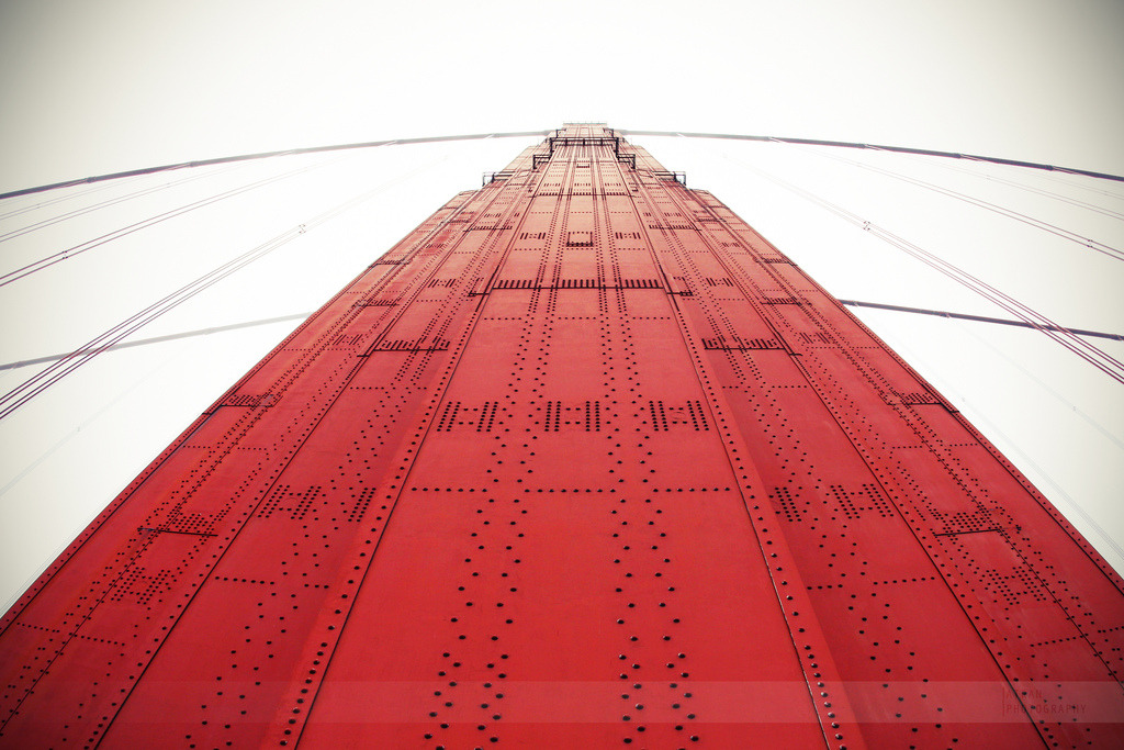 "Looking up at the south tower of the Golden Gate Bridge. This day was the last full day I had in San Francisco. My family finally was able to park near the Golden Gate and walk on it for a bit. It was a usual foggy day in SF, and it wasn't as windy. We walked starting from the south entrance and it was somewhat breezy and I thought, ""Hey, this is fine!"" Little did I know that when we got further down it was way windy. Amy and I made it a little past the south tower and then turned around and went back. The howling winds and speeding cars was pretty scary.  We took some jumping shots (as usual for us) near the tower. My external flash came in handy as a fill-light on the foggy bridge. While returning, I found an Eneloop battery: a sign that other photographers with external flashes were here too!"
