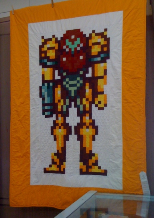 This is a super awesome Metroid quilt from my county fair (Mendocino County, CA last fall). It placed but I've since forgotten what category it won and who did it. Damn this makes me want to pick up quilting too. :-) I heart textile crafts!!