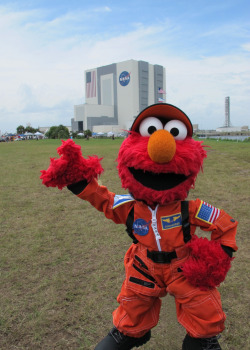 sesamestreet:  During his trip to NASA, Elmo got to see the Vehicle Assembly Building (that big building in the background). It's the largest single story building in the world and its doors are the biggest anywhere, stretching over 450 feet up!