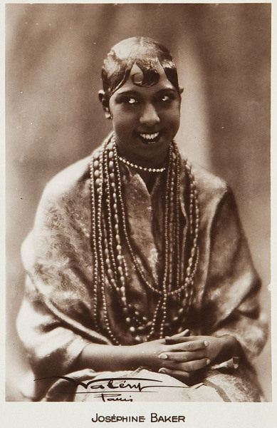 "Josephine Baker (France, 1930s). French Postcard Photo (3.5"" X 5.5""). Vintage sepia toned postcard, studio name in the lower portion of the card."