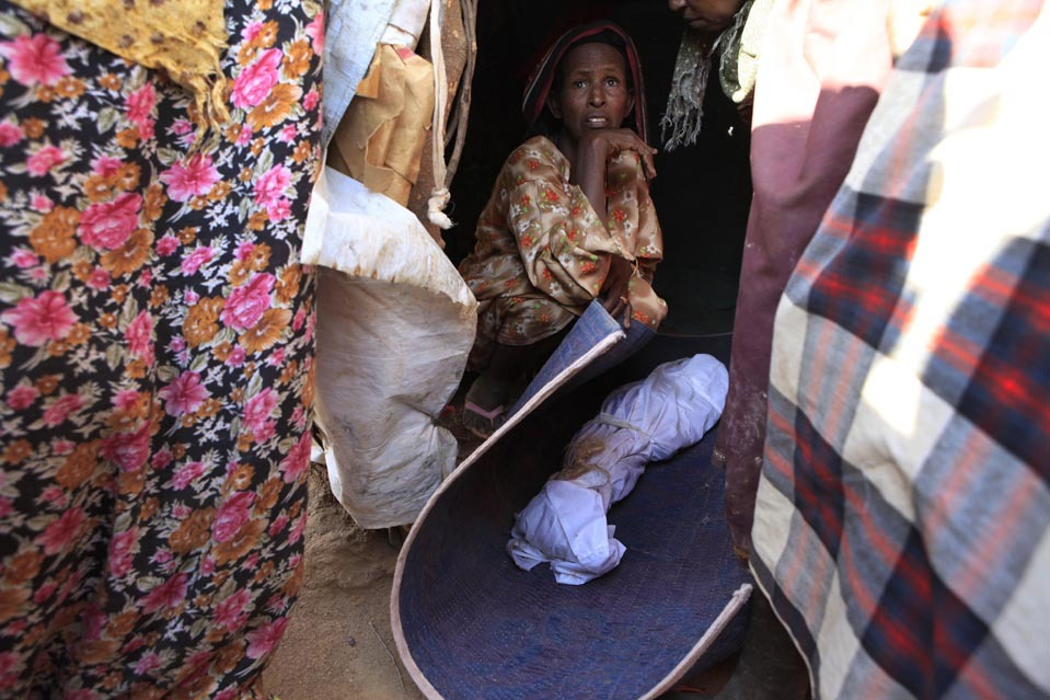 "pantslessprogressive:  Kenya. July 12. The body of Nasro Ahmed Gure, 3, was prepared for burial in Dadaab, Kenya, Tuesday. Relatives said the young Somali refugee died of malnutrition. Dadaab is the world's largest refugee camp, where many Somali refugees live. Dadaab was built to house 90,000 refugees, yet its population exceeds 370,000. On Sunday, the UN's refugee agency (UNHCR) said Somalia is enduring the ""worst humanitarian disaster"" in the world. [Photo: Rebecca Blackwell/AP]"
