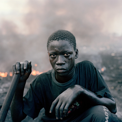 "© Pieter Hugo, 2009-2010, Abdulai Yahaya, Agbogbloshie Market, Accra / Ghana This photo is part of the exhibition 'Pieter Hugo - This Must Be The Place / Selected Works 2003-2011'. Exhibition Dates:Mar. 3 - May 20, 2012 at The Hague Museum of Photography in Den Haag / Netherlands. ""The South African photographer Pieter Hugo's (1976) monumental photographs, centred around contemporary Africa, are now well known around the world. The Hague Museum of Photography will be the first museum to exhibit a comprehensive survey of Hugo's work from 2002 – 2011. Together with many previously unseen works, the exhibition will include a curated selection of his most well-known series: The Hyena & Other Men, the bizarre Nollywood and the striking Permanent Error. In the series Permanent Error (2009 – 2010) he offers portraits of young men and woman who live amidst an immense waste dump of broken computers, mother boards and keyboards. To earn money these young people burn the computers dumped here as a means to extract valuable metals. The dangerous and poisonous vapours produce a hell on earth, where the quality of life is already challenging. The people who pose for Hugo stand in front of the camera with a defiant self-confidence."" (read more; thanks to ArtBlart) burnedshoes:  South African photographer Pieter Hugo's latest book, Permanent Error, pictures Agbogbloshie, a Ghanaian dumping ground for global electronic waste and home to slum-dwellers willing to endanger their health burning the techno-trash to harvest precious metals. The area is referred to by local inhabitants as Sodom and Gomorrah, a vivid acknowledgment of the profound inhumanity of the place. When Hugo asked the inhabitants what they called the pit where the burning takes place, they repeatedly responded: ""For this place, we have no name"". Related post: Nyaba Leon Ouedraogo - 'The Hell of Copper' ('L'Enfer du Cuivre')  » find more exhibitions here «"