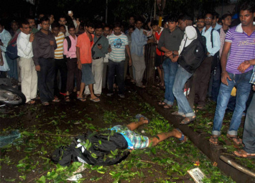 People crowd around a blast victim at Dadar bus stand in Mumbai on Wednesday.