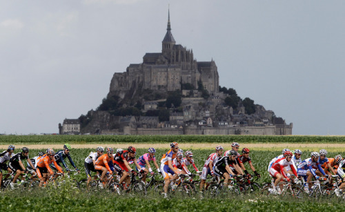 theatlantic:  Tour de France 2011 - Part 1  The 98th Tour de France cycling race kicked off on July 2, as 18 teams of nine riders departed from the the Passage du Gois in western France. Mark Cavendish of Britain just won the 11th stage of 21, which took place today in Lavaur, but French rider Thomas Voeckler still wears the yellow jersey of the overall leader. The first half of the tour this year has been plagued by crashes, most notably Netherlands rider Johnny Hoogerland's tumble into a barbed-wire fence after being bumped off the road by a car. The Tour continues until July 24, heading into the Alps for grueling mountain stages in the second half of the race. The entire tour will cover a distance of 3,430.5 kilometers (2,132 miles).  Above: Tour de France cyclists pass the world heritage site Mont Saint Michel, a rocky tidal island which holds a monastery, during the sixth stage of the racee in Lisieux, Normandy, western France, on Thursday July 7, 2011. (AP Photo/Laurent Cipriani)  See more awesome photos at In Focus