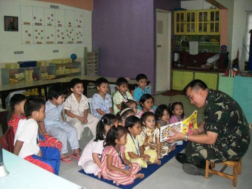 "Soldier and Kids for a Story Time Children pay attention to the friendly soldier, Major Eugenio Julio Osias IV, as he tells them a story from a storybook entitled ""Clifford"""