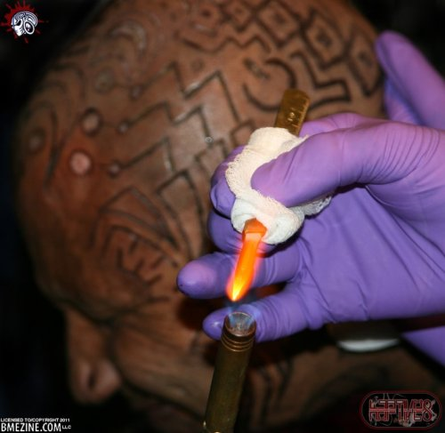 Supa Niga having his head branded. For this style of branding a scalpel is heated and then the design is cut into the skin, being cauterized simultaneously.