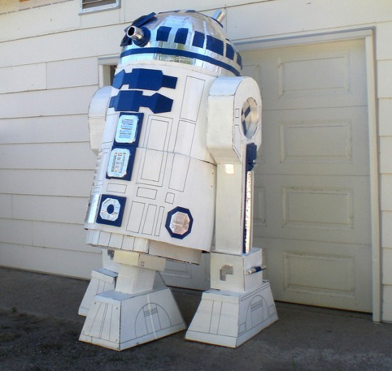 "Star Wars Fan Builds Giant R2D2 Model  From the man who brought you the awesome duct tape AT-AT comes one of the coolest R2D2 models ever made. Len Komanac, better known as DarthLen,  onFlickr, loves to build detailed models of Star Wars icons, using  cardboard, duct tape and glue. His detailed AT-AT model became an online  when photos of it hit the interwebs, last year, and now he's ready to  wow you once more with a giant replica of everyone's favorite droid,  R2D2. Towering at 96 inches/240 cm, this free-standing sculpture is made  from cardboard, silver HVAC tape and blue duct tape. Len was kind enough to send us a list of the materials he used to  complete his masterpiece: 4 fridge boxes, 5 AC boxes, 3 dryer boxes, 3  rolls of blue duct tape, 1 roll of aluminum tape, 52 glue sticks, 1 can  of white paint and 2 sharpie pens. He worked on it for 50 hours.  This  supersized version of R2D2 will be showcased at the ""Dr. StrangeLen or  How I Learned to Stop Worrying and Make the Art"" exhibit, in Lethbridge,  Alberta, Canada, so if you're in the area between July 16 and September  2nd, don't miss the chance to check it out.  (vía Oddity Central)"