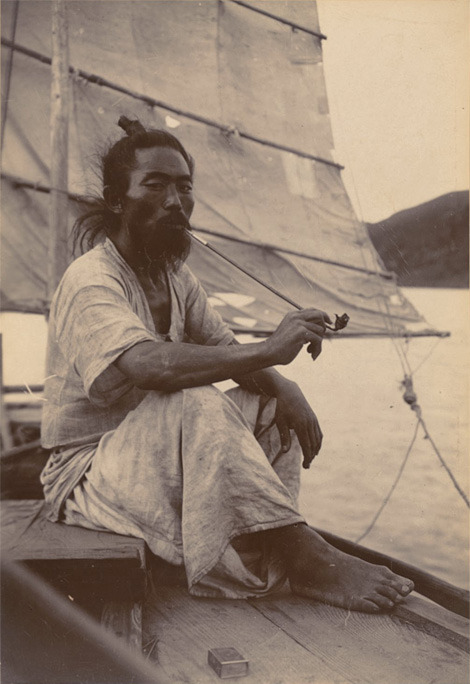 "andrewharlow:    ""Korean sailor takes a break from trasporting cargo and people, sitting under the shadow from the sail, smoking from his long bamboo pipe. He wears cool hemp clothes."" From the Cornell University Library collection."