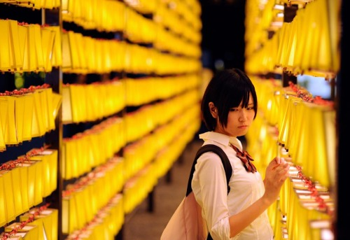 inothernews:  A woman stood between aisles of lanterns during the annual Mitama  Festival at Yasukuni Shrine in Tokyo Thursday. Thousands of paper  lanterns are lighted in honor of the dead. (Photo: Franck Robichon / EPA via the Wall St. Journal)