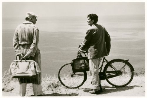 Massimo Troisi holds a bike. Philippe Noiret holds a bag.