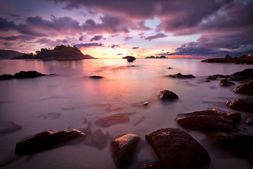 Morning Glow at Redang by CJ Dias Abeyesinghe on Flickr.Via Flickr: The cove of Laguna Redang lit up by the rising sun, Redang Island, Malaysia.View Large The early morning walk to the beach and the slippery rocks was well worth it. The cove conveniently has a rocky area to the right side of it which made an interesting setting to shoot from. Notes: Manually blended 3 exposures for this image through careful layer masking. The base image is the longest exposure. Couldn't use my GND here because the bright area is in the middle of the frame. Mild curves adjustment and USM sharpening thereafter. 450D | EF-S 10-22mm f/3.5-4.5 USM ISO100 10mm f/7.1 20sec (base image) EXPLORED!