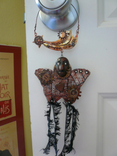 Steampunk wings door hanger. For a swap. I just realized the polyclay face I included on it looks like Terminator Grace Jones! XD