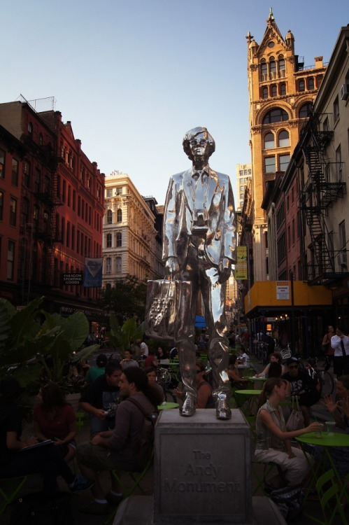 "nythroughthelens:  The Andy Monument, a tribute to Andy Warhol. Union Square, New York City. This is a public art installation tribute monument of Andy Warhol by artist Rob Pruitt. It went up at the end of March and will be on view in Union Square until October. It is situated on this particular corner since this is where Andy Warhol would stand when he signed and gave away copies of Interview magazine. It is also just steps away from the Factory: ""In 1968, Andy moved the Factory to the sixth floor of the Decker Building, 33 Union Square West, near Max's Kansas City, a club Warhol and his entourage would frequently visit. By the time Warhol had become famous, he was working day and night on his paintings. To create his art, Warhol used silkscreens so that he could mass-produce images the way capitalist corporations mass produce consumer goods. In order to continue working the way he did, he assembled a menagerie of adult film performers, drag queens, socialites, drug addicts, musicians, and free-thinkers that became known as the Warhol Superstars, to help him. These ""art-workers"" helped him create his paintings, starred in his films, and basically developed the atmosphere for which the Factory became legendary. Aside from his two-dimensional art, Andy also used the Factory as a base to make shoes, films, commissions, sculptures and just about everything else that the Warhol name could be attached to and sold. His first commissions consisted of a single silkscreen portrait for $25,000, with additional canvases in other colors for $5,000 each. He later made that $20,000. Warhol used a large portion of his income to finance the lifestyle of his Factory friends, practically showering them with resources. - Source — Buy ""The Andy Warhol Monument"" Posters and Prints here, email me, or ask for help."