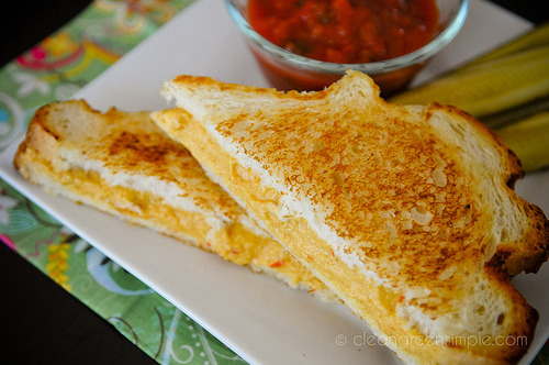 Vegan Grilled Cheese Ingredients: 1 1/3 c. water 1/2 c. roasted red peppers (skin & seeds removed) or pimiento pieces 1/3 c. quick-cooking rolled oats 1/4 c. nutritional yeast flakes 3 Tbsp. fresh lemon juice 2 Tbsp. kuzu, arrowroot or cornstarch 1 Tbsp sesame tahini 2 tsp onion powder (I used about 2 Tbsp fresh chopped onion) 1 1/4 tsp salt 1/4 teaspoon each: garlic powder (I used 2 cloves chopped garlic), ground dill seed or coriander, dry mustard, and paprika. Pinch of cayenne 8-12 slices of bread (use rice bread to make this recipe gluten free) Tomatoes or salsa (optional) Directions: Combine all ingredients except bread and tomatoes, in a blender or food processor until completely smooth. Pour into a medium saucepan and bring to a boil, stirring constantly. Reduce heat to medium low and cook, stirring frequently, until mixture is very thick and smooth. Remove from heat. Spread about 3-4 Tbsp of mixture each onto half of the bread slices. Top with a slice of tomato or some salsa, if desired, and remaining bread slices. Heat in a large skillet (lightly misted with olive oil) over medium heat until golden brown, about 3 minutes per side. Cut diagonally and serve. Or cut straight across or don't cut it at all, I'm not the boss of you. (I whould recomend less lemon juice as you can taste it a bit other than that it was lush and lasted in my fridge for a week)