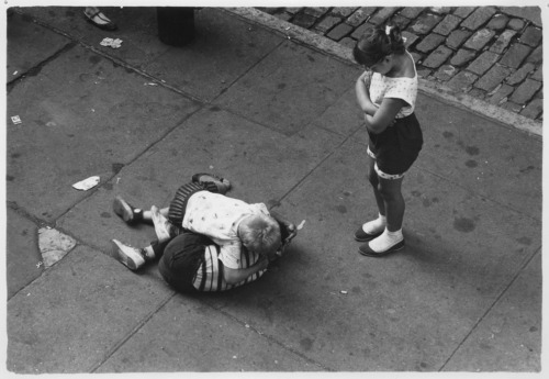William Gedney Boys wrestling on sidewalk with girl looking on. Myrtle Avenue, Brooklyn, 1959