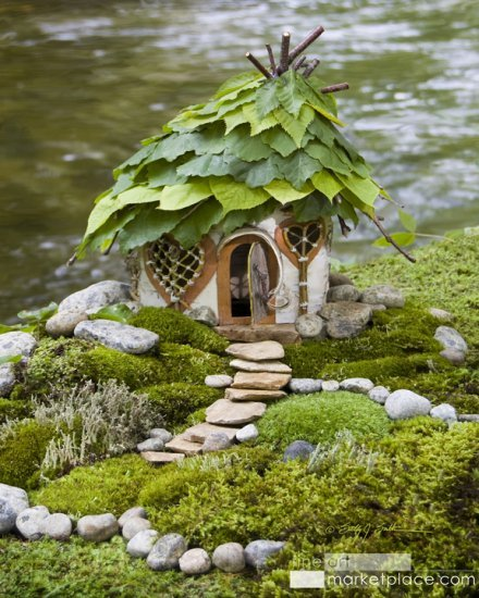 Hazel Leaf Faerie House by Sally J. Smith. A faerie house made of birch bark with woven twig windows and a hazel leaf roof on the edge of a cool stream.