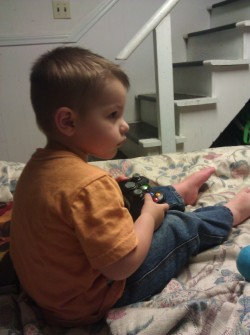 "My two-year-old nephew playing his first video game. He says ""Mario"" all the time, thanks to my giving him a Super Mario Bros. DVD, but it was Banjo Kazooie he got a hold of first. All he could do was jump up and down and run around, but he was pretty pleased with himself about that. Also, just to give him a nerdy-enough setting, there is a collection of Buffy comics behind him you can just barely see on the left, and a Dragon Quest Slime plushy to his right. My sister will probably eventually come to regret the time he spends with me."