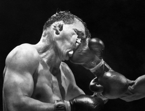 Gene Fullmer receives a crushing right from Neal Rivers during their 10-round bout at Madison Square Garden. Fullmer, a former middleweight champion, would go on to win the bout by a majority decision.  This Sporting Life