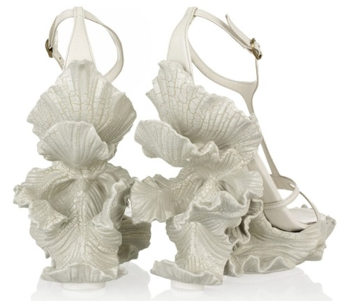Lovely sculpted resin shoes by Alexander McQueen, for the fairy queen in every one of us. From Fashionising:  The fashion house of Alexander McQueen illustrates just how design brilliance doesn't end at the ankles, but goes all the way till the bottom of the feet. These intricately designed wedges, part of the McQueen spring 2011 collection, are a classic embodiment of artistic surrealism. The crisp, but gentle flower petals curve around the edges of the leather platform creating a perfect balance between design and wearability. Almost exhibiting a Grecian bride look, this creation by Sarah Burton is a true amalgamation of fashion and art.  (Image via Fashionising)
