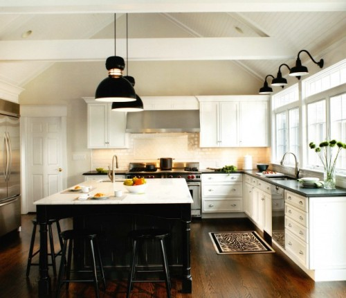 contrasting cabinets - white cabinets with black counters on outside, black counters with white counters on island stunning black light pendants large stove/hearth hardwood floor windows beadboard on ceiling  not many upper cabinets but that huge island makes up for it hardwood backsplash
