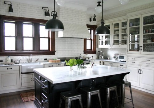 Here's another kitchen with contrasting cabinets. contrasting cabinets - black island with white counter, white outer cabinets with white counters wish the trim on the windows was black instead of dark brown custom cabinets on far wall - gorgeous, lots of storage subway tile walls all the way around (don't like them on the stove hood though - would prefer stainless) black light fixtures like the industrial touches - stools, lighting, even the subway tile - adds interest to an otherwise very traditional kitchen farmhouse sink