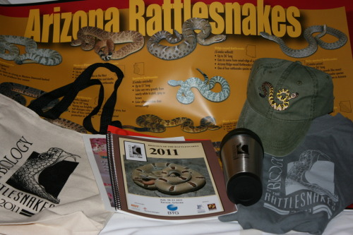 Biology of the Rattlesnakes Symposium: Part 1 So I was a bit starstruck by seeing quite a few famous rattler herpetologists waiting in line to register… but I think I'll get over it soon (so I can talk with some of them). We got a ton of awesome free stuff (and some purchased stuff- bought the hat and the shirt) and there was an amazing display of live rattlesnakes. It was really funny when they rolled them in, they were in their display tanks on the cart being pushed by the front desk staff. I wonder if they had to pay extra to the hotel to bring in live venomous reptiles…  I can't wait for tomorrow!!