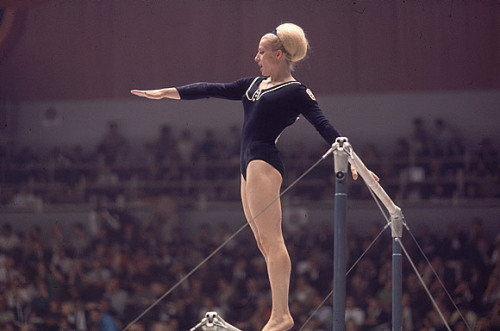 Věra Čáslavská, Mexico City, 1968 Born in 1942, Czech gymnast Věra Čáslavská dominated gymnastics in the 1960s.  She  won a total of 22 international titles, including seven Olympic gold medals in individual events, more than any other gymnast.  Only Micheal Phelps has won more individual Olympic gold medals.  Two months before this photo was taken, Soviet tanks rolled into Czechoslovakia, ending the temporary political liberalization of Prague Spring.  Věra was well known for her support of the democratization movement, as well as her opposition to the Soviet invasion.  Her political position endangered her ability to participate in the Mexico City games but at the last minute she was granted permission to travel by the government.  Once in Mexico, Věra's performance was excellent and she won the individual vault, uneven bars, and all around.  She initially appeared to win gold in the floor exercise until the judges upgraded the preliminary score of Soviet gymnast Natalia Kuchinskaya, creating a tie.  In the end, Věra won three gold medals and two silver medals in Mexico City. For two individual medal ceremonies, floor and beam, the Soviet anthem played and Věra silently looked down.  Her quiet protest of the Soviets led the government to force her retirement from gymnastics and restrict her travel, work and sports participation. In the late 1980s, pressure from the International Olympic Committee (IOC) led to the Czechoslovakian government granting Věra permission to work as a coach.  After the 1989 end of communism in Czechoslovakia, Věra fully entered public life again. She became an advisor to President Václav Havel and Honorary President of the Czech-Japan Association.  After leaving the President's Office, she was elected President of the Czech Olympic Committee and was appointed to the IOC membership committee.   Today, Věra lives quietly in Prague.