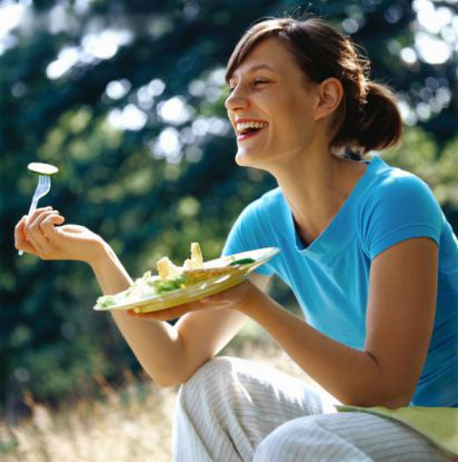 Women laughing alone with salad   Still funny.