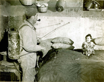 GI spraying a DDT/kerosene mixture in a southern Italy house, during post-WWII Mediterranean antimalarial campaign. 1945. I love how he's smoking a pipe while spraying kerosene and DDT on a child.