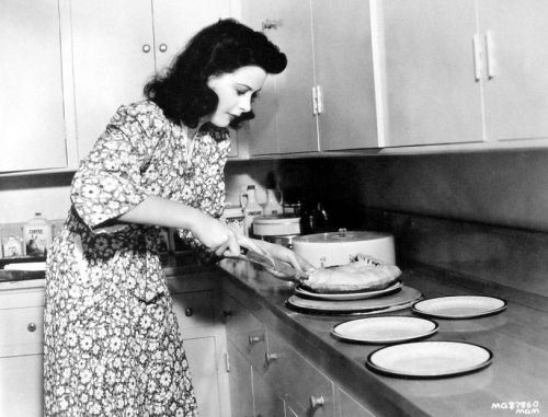Hedy Lamarr slices a pie at home - c. 1940s