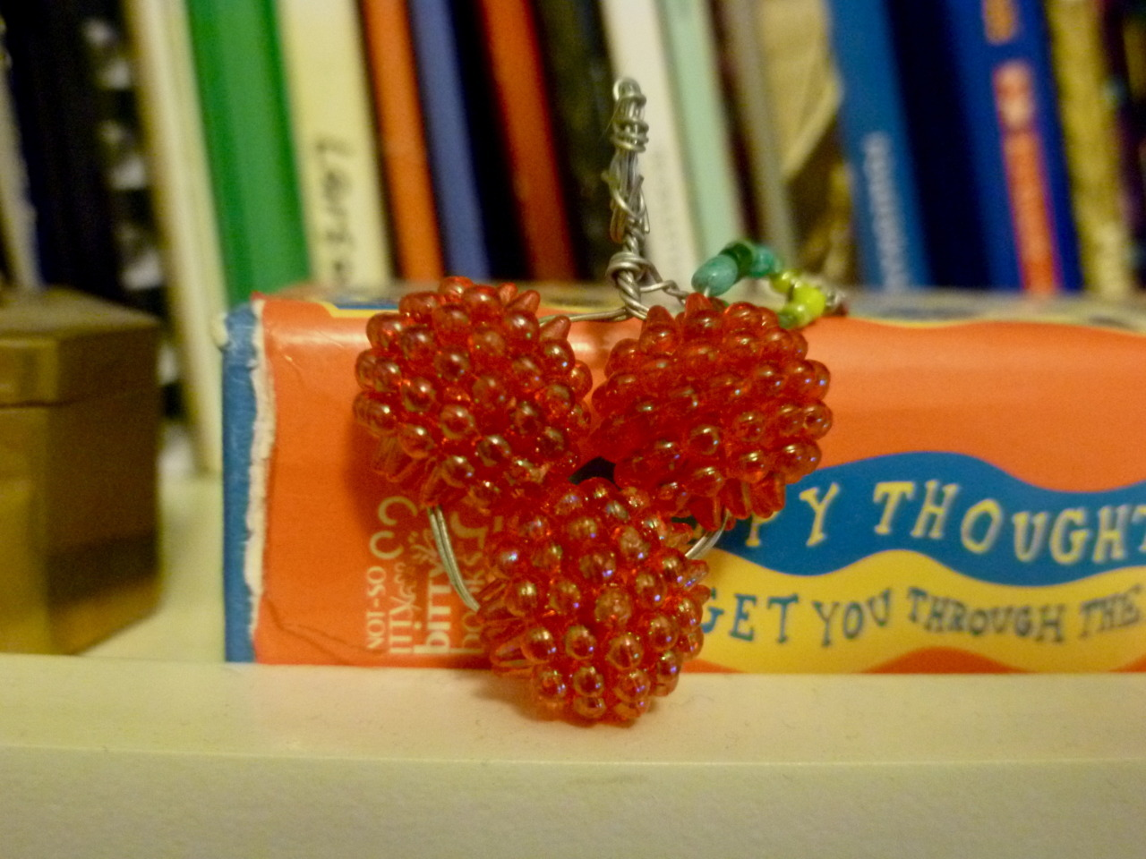 Strawberry pendant. I don't know if you can see the leaf, but its wire with green seed beads on it.