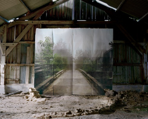 "This is Noemie Goudal, who is part of Photography As Object at the Sumarria Lunn gallery. My review in Whitehot Magazine is here. ""Goudal has re-photographed her images of a bridge or a tropical landscape inside a gritty environment, creating windows into other worlds. But the illusion is fractured, as the idyllic images are printed on several pieces of A3 paper and the gaps in between are clearly visible. Still, you can't help but want to go there, stepping first into the barn or warehouse where the shoot took place, and from there on into nature. You can see the illusion isn't real, but it doesn't matter, you want it anyway."" - - - Also, my review of Christoph Büchel's Piccadilly Community Centre is out now in This Is Tomorrow, here."