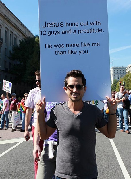 "lgbtlaughs:  [a man in a grey t-shirt wearing sunglasses holding a sign: ""Jesus hung out with 12 guys and a prostitute. He was more like me than you.""]  Ohmahgod perfect sign."