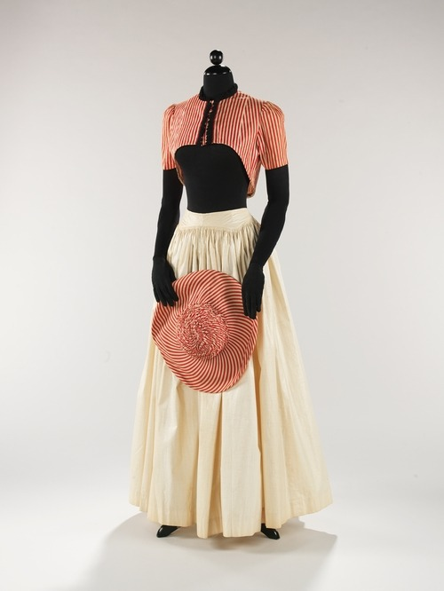 A lovely summer ensemble of a skirt, bolero and matching hat from Elsa Schiaparelli's Spring-Summer 1940 collection. Edit to clear things up for baconistasty and anyone else who may be confused… The top is a bolero jacket so it would have presumably been worn over a blouse, possibly even a midriff blouse which were in style at this time, but there would have definitely been more skin coverage than on the manikin. I believe (though it's a complete guess) the reason the museum (the Met in this case) chose to display it this way is because the original Schiaparelli ensemble did not include a blouse.  (I did a double take the first time I saw it as well ;) )