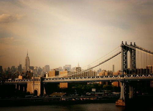 "The Manhattan Bridge and the New York City Skyline.  In an earlier post, I mentioned how freeing it was for me to finally discard the jadedness that permeated my early years growing up here in New York City. It was then when I started to realize how utterly phenomenal and fascinating all the things I went out of my way to avoid truly are.    I started taking photos a few years back in a rather stream of consciousness manner. I don't drive since I live in New York City and without much in the way of material things or financial prosperity walking became a way to deal with stress. It also became the main way to experience New York City in a way I hadn't experienced the city before. I would choose a direction and walk as far as my feet would take me (I still do this). I started noticing lines, forms and structures I had previously ignored. Scenery unfolded before me as if it was just rendered before my eyes.   To embrace my new-found sense of wonder, I decided to take the only camera I had at the time with me on these walking adventures. It was a simple point and shoot which was less than $100. It was all I could afford at the time and I just wanted to be able to record the moments and experiences that made my heart swell.  After doing this for several years, I decided to start posting my photos online to keep a record of some of my walking adventure photos. It didn't occur to me that there would be an audience for my photography. I had no formal training in photography and no real knowledge of the rules or major concepts that defined the field.   The website I started posting on a year ago is now where my main site points to (this Tumblr). It's been quite a journey since I posted those first few photos online.  Somehow, along the way I ended up on the receiving end of a variety of experiences that have changed my world in a truly dramatic manner. While I am still trying to figure out ways to make photography financially viable, I am so appreciative of the many opportunities I have had come my way. With around 20,000 followers currently on Tumblr, I am extremely appreciative of all of the private messages and notes as well as the bevy of talented people I have met along the way.    A wonderful person on Google Plus shared a quote recently by Henri Matisse that really resonated with me: ""a large part of the beauty of a picture arises from the struggle which an artist wages with his limited medium.""  I think that there is a tremendous amount of truth in the sentiment that when you are limited you are forced to work extremely hard to get the results you desire.  The photo in this post was taken on one of my walks across the Brooklyn Bridge. One of my favorite things to do is walk over any of the bridges in lower Manhattan. Each offers a completely different view of New York City and each time I cross any one of them, I still feel butterflies in my stomach as the views of the city's skylines come into sight.   I hope I never lose that feeling of pure and unadulterated wonder.    —-  View this photo larger and on black on my Google Plus page   —-   Buy ""The Manhattan Bridge at Sunset"" Posters and Prints here, Other versions of this print with writing and various borders can be viewed  here (any of them can be customized to have whatever background you desire): ""The Manhattan Bridge at Sunset"" with Black Border, ""The Manhattan Bridge at Sunset"" with White Border, ""The Manhattan Bridge at Sunset"" with Grey Border, View my store, email me, or ask for help."
