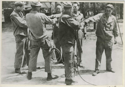 1942. Troops getting dusted with DDT mix to eliminate typhus-causing body lice living in the clothing.