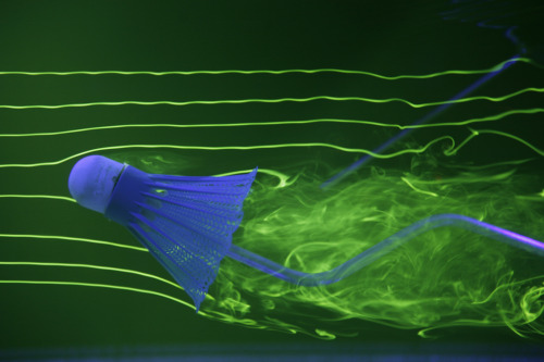 The flow around a shuttlecock is visualized in a water channel using fluorescent dye illuminated by laser light ultraviolet LEDs. Note the recirculation zone on the upper shoulder. Experimenters can match flow characteristics in water to that in air by matching the Reynolds numbers. (Photo credit: Rob Bulmahn) Updated, thanks to information from the photographer. Thanks!