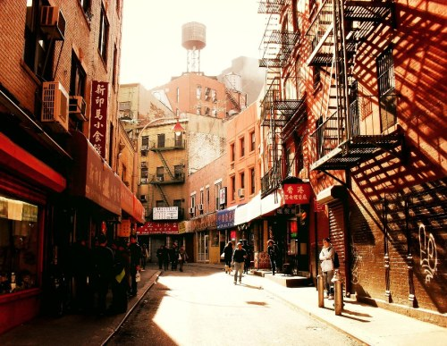 "Doyers Street. Chinatown, New York City.  Out of the way streets tell a wealth of tales. The bright afternoon sun beats down on old decaying walls and fire escapes creating elongated shadows that seem to stretch indefinitely. If the well-worn awnings could talk, just think of the secrets they would reveal.  This particular photo is of Doyers Street, one of my favorite out of the way streets. It is a winding street that curves around and is tucked away from its hectic surroundings. The street is only about 200 feet long and runs from Pell Street to Chatham Square. It's home to very old tenements and long-standing businesses like The Nom Wah Tea Parlor which opened in 1927.   In the early 20th century the curve in the street was known as ""the Bloody Angle"" because of a plethora of violent acts carried out by Chinatown gangs. The expression 'hatchet man' is said to have come from this era and these violent acts which often included hatchets. While the street is not bloody or violent today, it's worth a visit to soak in the history, vibe and incredible scenery.   —-  View this photo larger and on black on my Google Plus page   —-  Buy ""Wealth of Tales - Doyers Street - Chinatown - New York City"" Posters and Prints here, email me, or ask for help."