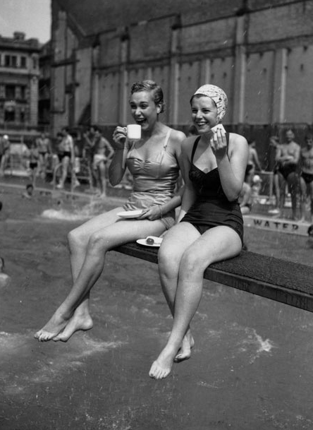 maudelynn:  Two office workers choose the diving board at the Holborn Oasis swimming  pool in London as the coolest place to eat their lunch during the  heatwave of August, 1955 Photo by Monty Fresco