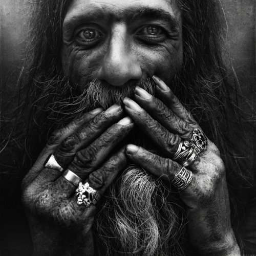 An account by day, Lee Jeffries started his stunning series of portraits of the homeless after a young girl, huddled under a sleeping bag in the streets of London, caught him snapping a candid shot. Instead of walking away, the photographer came over to talk to her. After hearing her story, he could no longer sneak shots at distance. These portraits of people from Europe and United States, spotted by Dangerous Minds, reveal incredible detail — graying ringlets of a long and tattered beard, an eye clouded with glaucoma, wind-blown strands of hair caked with cigarette ash, ridges of deep wrinkles and scrapes. They also reveal the real intimacy that needed to be established between the subject and the photographer in order to capture an image that feels authentic as opposed to exploitative. Photo Gallery: Dramatic Portraits of the Homeless